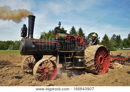 Amish steam tractor engine plowing the field in Middlefield, Ohio in Summer August 30, 2016