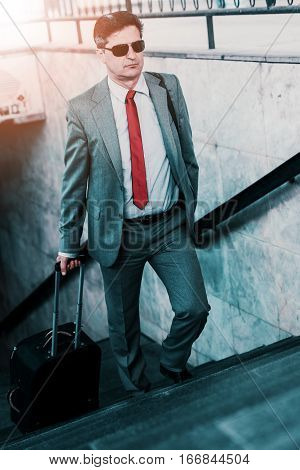 Elegant businessman walking with suitcase outside airport.Businessman traveling concept.