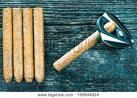 Group of cigars and cigar cutter on the dark brown wooden surface. Flat lay. Color toning