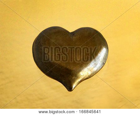 Antique bronze figurine heart isolated on golden background