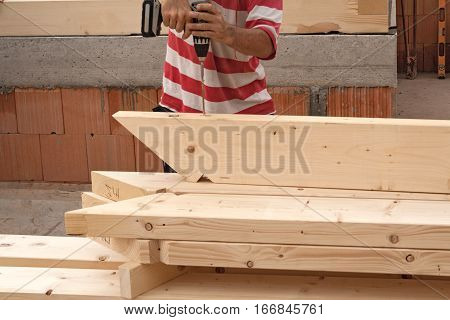 A carpenter when drilling several roof beams