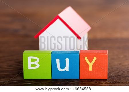 Small House Model With Word Buy On Multi Colored Blocks