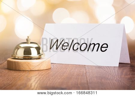 Service Bell With Welcome Card On Wooden Desk In Hotel