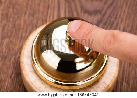 High Angle View Of Person Ringing Service Bell On Wooden Desk In Hotel
