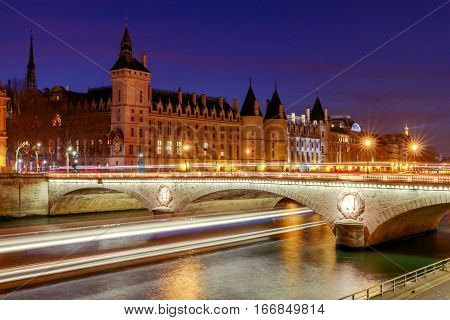 Embankment along the Conciergerie and the river Seine at night. Paris. France.