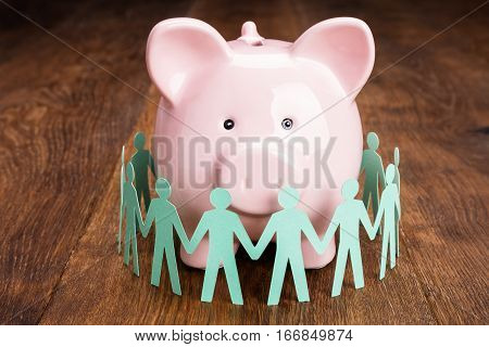 Close-up Of Papercut Surrounded By Piggybank On Wooden Desk