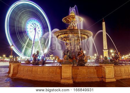 Obelisk fountain and a Ferris wheel on the Place de la Concorde at night lighting. Paris. France.