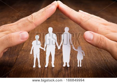 Close-up Of Person Hand Protecting Family Papercut At Wooden Desk