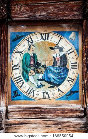 ORTISEI, ITALY. March 28, 2016: Tower clock in wooden frame with history painting in the main square of Ortisei in Italy. Analog clock with roman numerals. Vintage retro wooden frame.