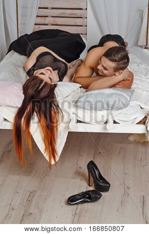 Young couple lying on  hanging bed suspended from the ceiling . He looks at her. White loft interior.