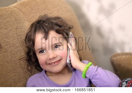 Cute little girl is talking on the mobile phone and smiling while sitting on couch at home. Small girl with smartphone. Girl talking on smartphone.  Little girl using smartphone. Smartphone in hand.
