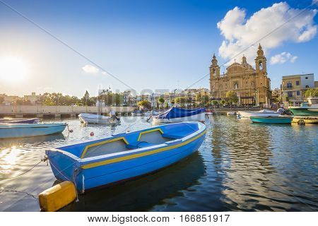 Msida Malta - Blue traditional fishing boat with the famous Msida Parish Church at background on a summer day with blue sky and clouds poster