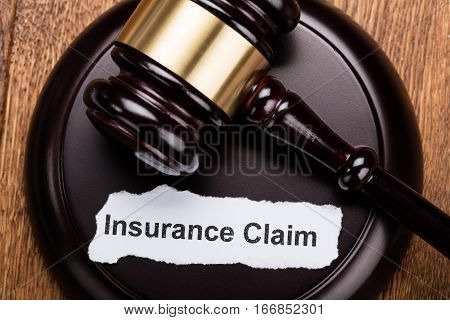 High Angle View Of Insurance Claim Concept On Wooden Gavel At Wooden Desk