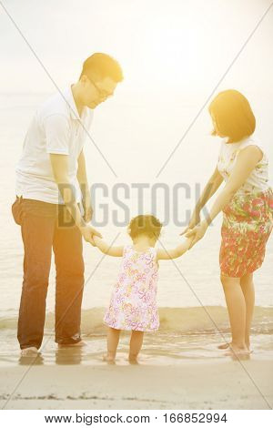 Happy Asian family outdoor activity, holding hands together walking at beach in sunset during vacations.