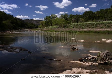 Puffy white clouds float above the Colorado River near Bend, Texas on a spring day