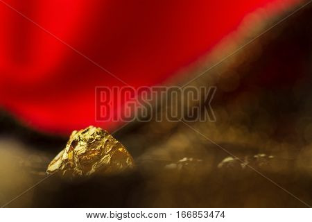 Golden nugget on red background with glitter
