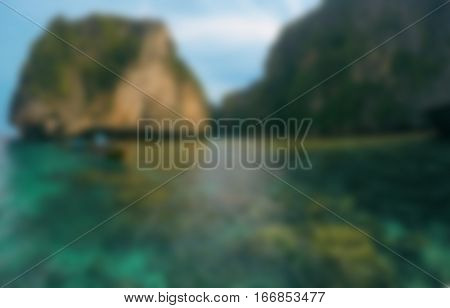 Warm tropical sea blurry photo background. Tropical beach blurry image. Seaside bokeh image. Abstract exotic island travel blurry landscape. Distant island and clear seawater blurry background