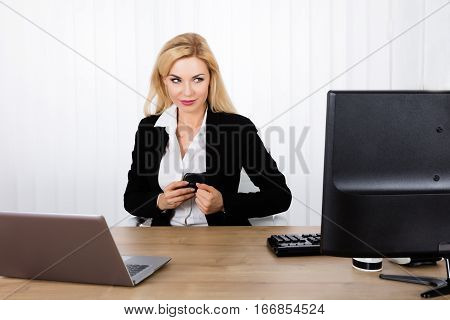 A Young Woman Stealing Computer Mouse From Office Desk