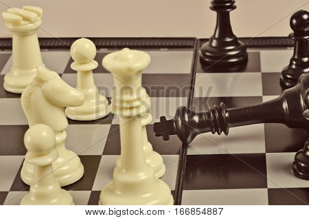 Black defeated chess king lying on the black-and-white board surrounded by other figures