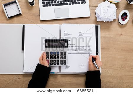 High Angle View Of A Accountant Calculating Invoice Using Calculator On Wooden Desk