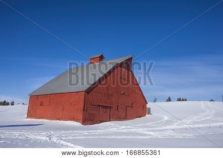 A red barn on the side of a small snowy hill in Moscow Idaho.