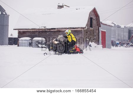 A man in motion tipping his snowmobile on the side for fun with an old barn in the background in a farm yard landscape