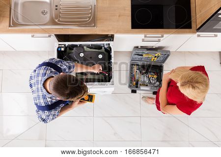 High Angle View Of Male Worker Repairing Washing Machine With Woman Standing In Kitchen