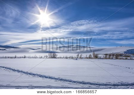 Sun shines over snowy fieldin Moscow Idaho.
