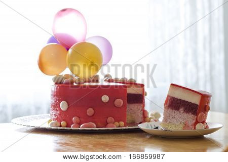 Homemade red birthday cake with air baloons. Slice of a red velvet cake on a plate.