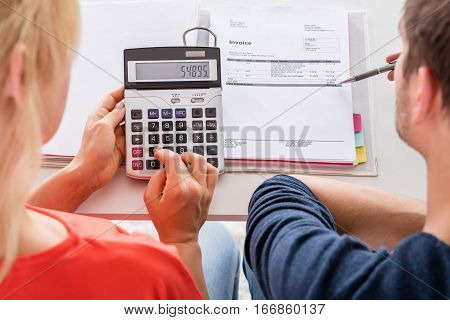 High Angle View Of Couple Calculating Invoice Taxes And Family Budget At Home poster