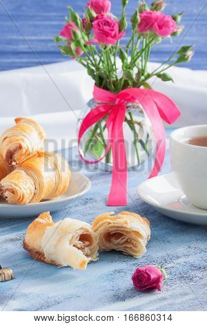 Breakfast With Croissants Tea And Flowers On Blue Wooden Tray.