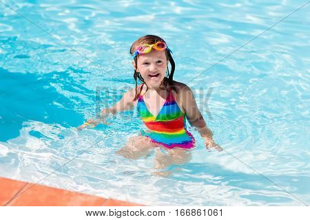 Happy little girl learning to swim and dive in outdoor swimming pool on hot summer day in tropical resort. Child wearing goggles and colorful bathing suit playing in water.