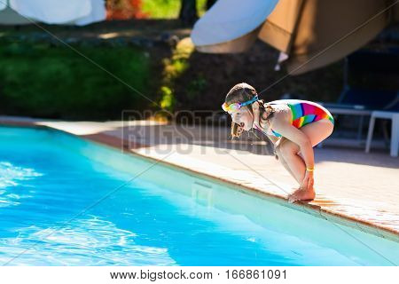 Happy little girl with inflatable toy ring jumping into outdoor swimming pool in a tropical resort during family summer vacation. Kids learning to swim. Water fun for children.