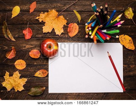A pencil on the empty paper an apple and autumn leaves on wooden table. Back to school concept: paper pencils apple and colorful leaves.