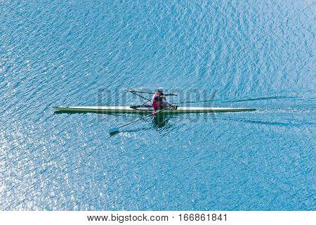 Men's single scull on lake , toned image