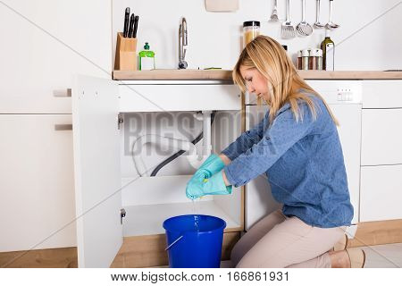 Young Woman Near The Kitchen Sink Squeezing Wet Cloth After Emergency Faucet Leakage