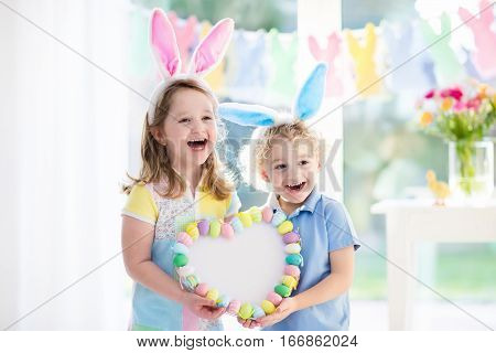 Little boy and girl in bunny ears holding a heart frame with colorful Easter eggs. Kids celebrate Easter. Children having fun on Easter egg hunt. Pastel bunny banner and flowers. Space for your text.