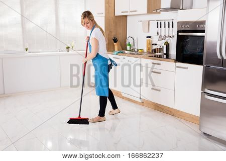Young Housemaid Cleaning Floor With Broom In Kitchen