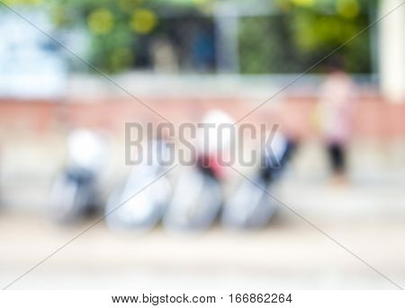 Abstract blur background with motorbikes. Street parking blurry view. Motorcycles parked by the greenery blurry image. Street view blur for background or banner template. Pink and green colors