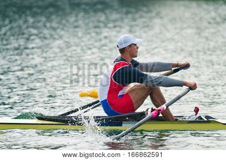 Single scull rowing competitor, on lake , toned image
