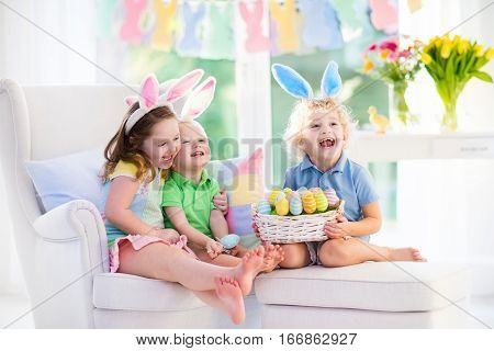 Kids celebrate Easter. Family happy little girl boy and baby in bunny ears on a couch. Children having fun on Easter egg hunt. Home decoration pastel bunny banner colorful Easter eggs and flowers