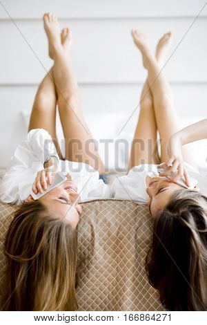 Two Stunning Women Talking On Phones With Their Hair Falling Off The Bed