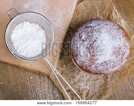 donuts with powdered sugar on a wooden table