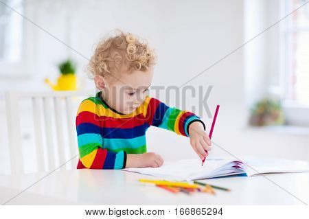 Cute little boy doing homework reading a book coloring pages writing and painting. Children paint. Kids draw. Preschooler with books at home. Preschoolers learn to write and read. Creative toddler