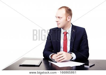 Businessman at a table with a tablet before signing the contract. Turn your head to the side. Isolated on white background
