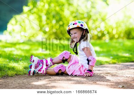 Little girl learning to roller skate in sunny summer park. Child wearing protection elbow and knee pads wrist guards and safety helmet for safe roller skating ride. Active outdoor sport for kids.