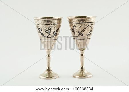 silver handmade stemware on the white backboard