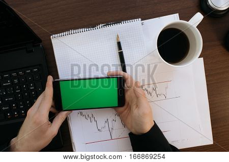 Side view of a man with a marker and stable standing against a concrete wall with graphs drawn on it. Concept of statistics and stocks With the green screen keying for smartphone