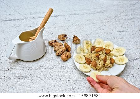 Healthy porridge of quinoa served with banana and almonds. Fresh morning breakfast