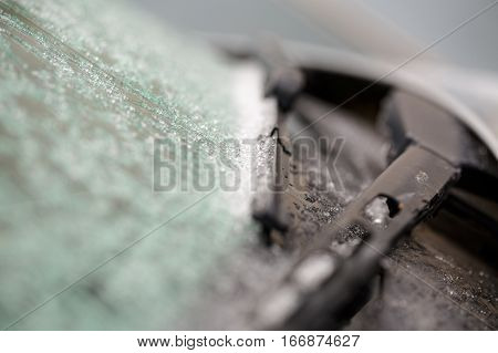 wipers covered in winter frost. natural frosty pattern on glass car. wipers and frosty background
